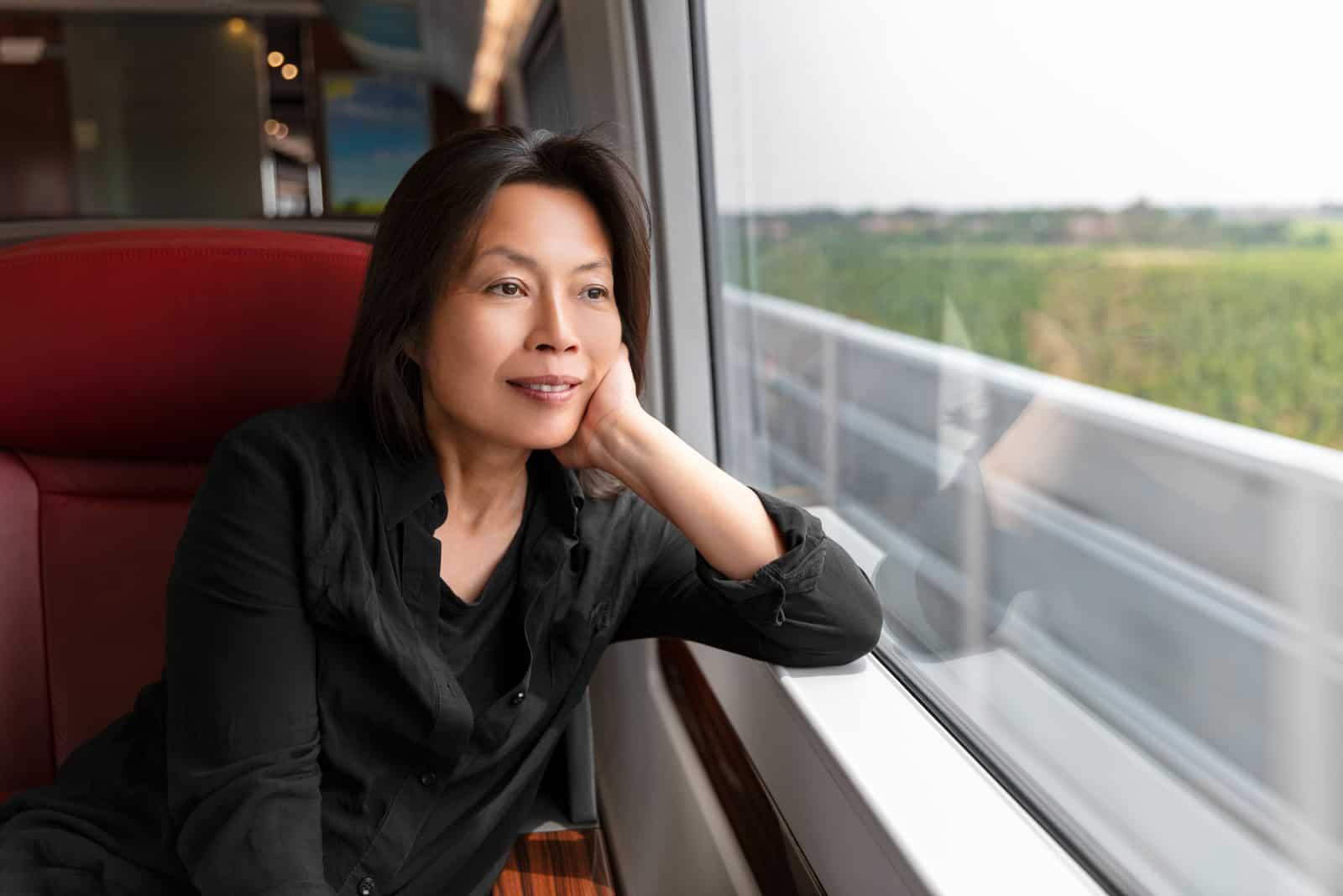 Asiatische Frau mittleren Alters, die aus dem Fenster schaut