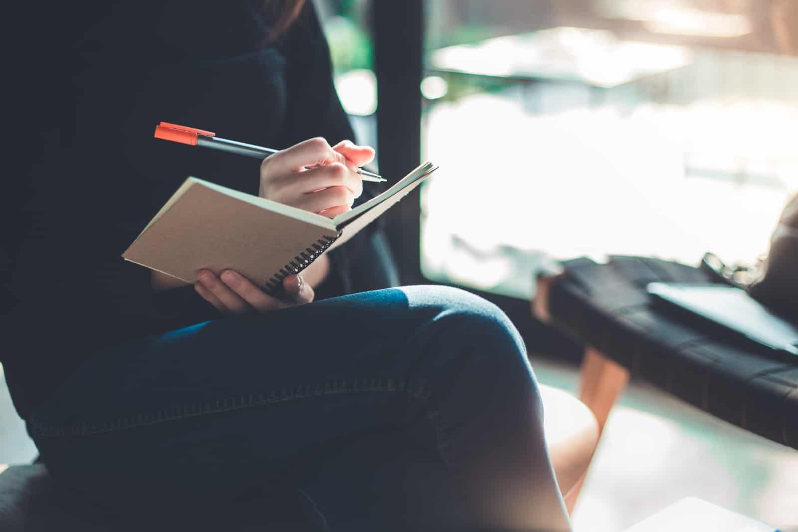 Das Mädchen sitzt auf einer Bank und macht sich Notizen