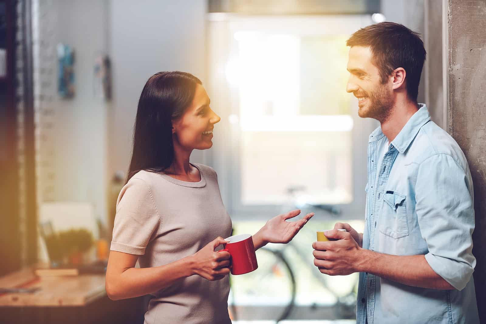 Ein fröhlicher Mann und eine Frau unterhalten sich beim Kaffeetrinken im Stehen