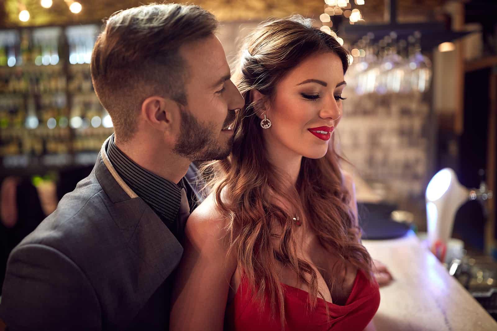 Ein Mann flirtet mit einer attraktiven Frau an der Theke