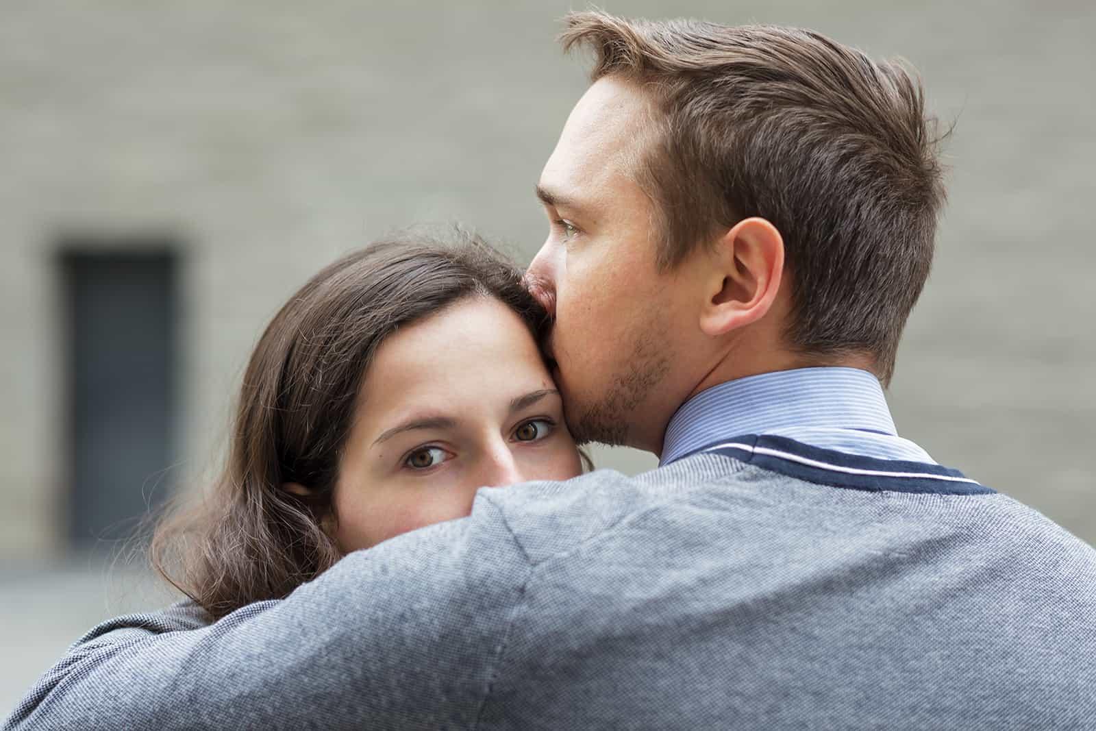 Ein Mann küsst eine Frau auf die Stirn, während sie zur Seite schaut