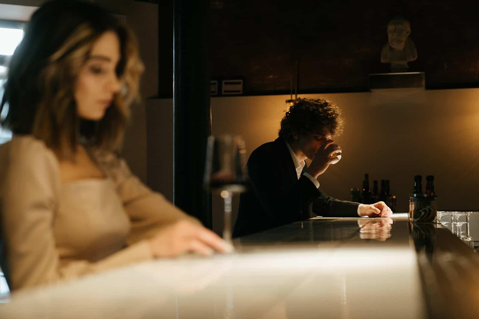 Ein Mann sitzt alleine an der Theke und trinkt aus dem Glas in der Nähe einer Frau