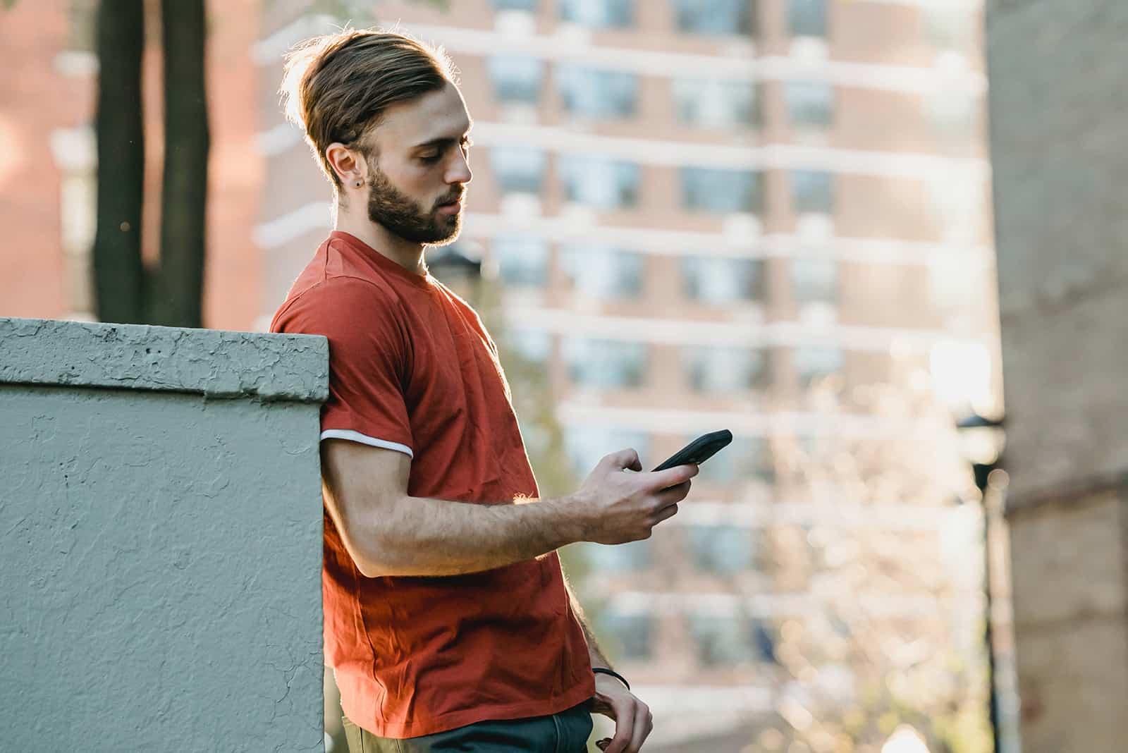 Ein Mann überprüfte sein Smartphone und lehnte sich an die Betonwand in der Straße
