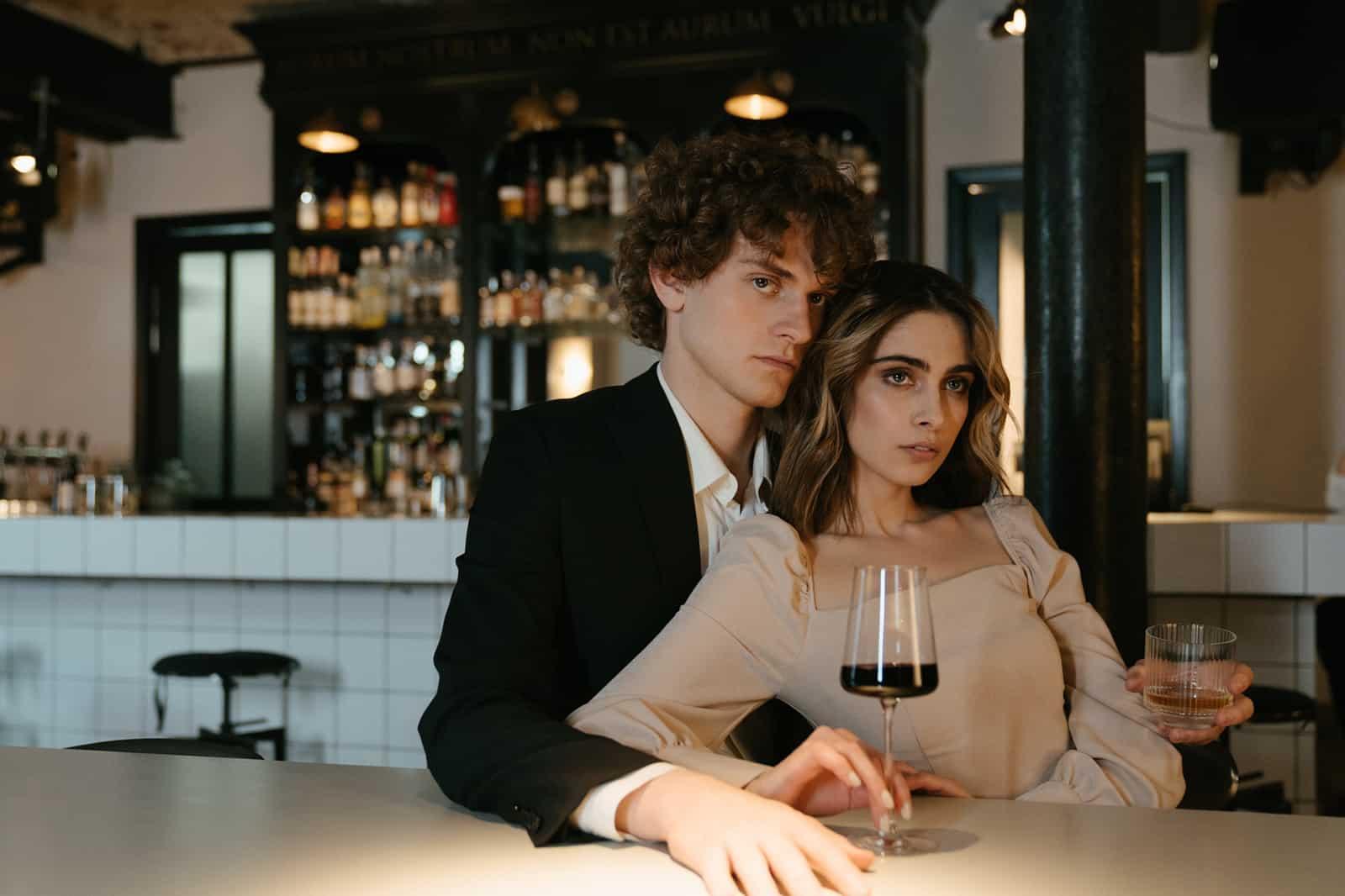 Ein Mann umarmt eine Frau von hinten, während er in der Bar sitzt und Wein trinkt