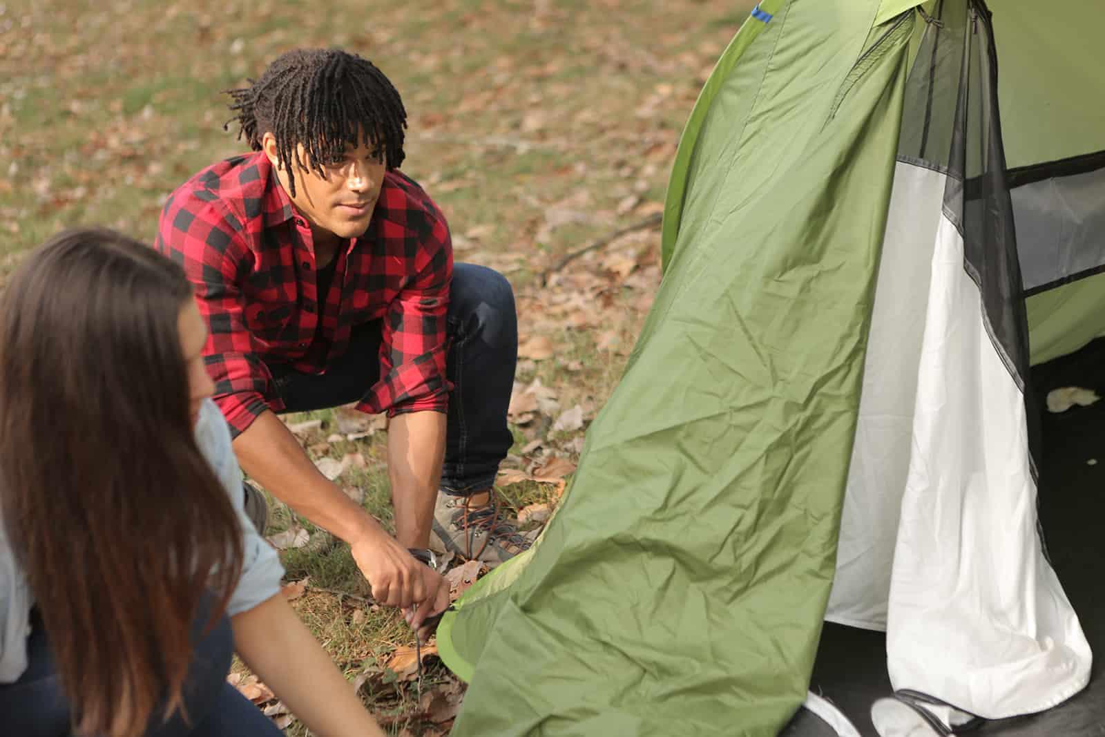 Ein Mann und eine Frau schlagen ein Zelt im Wald auf
