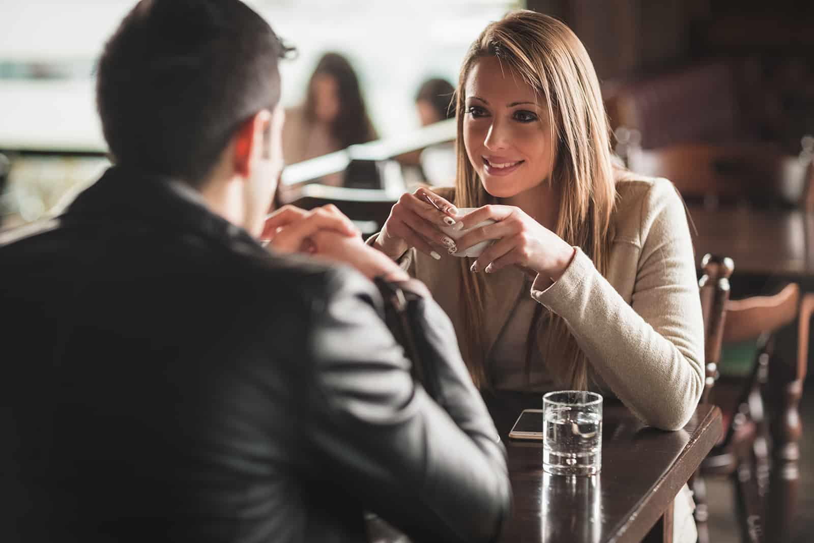 Ein Mann und eine Frau trinken Kaffee in der Bar und flirten
