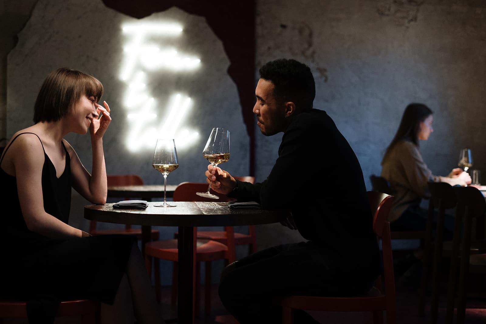 Ein Mann und eine Frau trinken Wein in einem Restaurant und unterhalten sich über ein Date