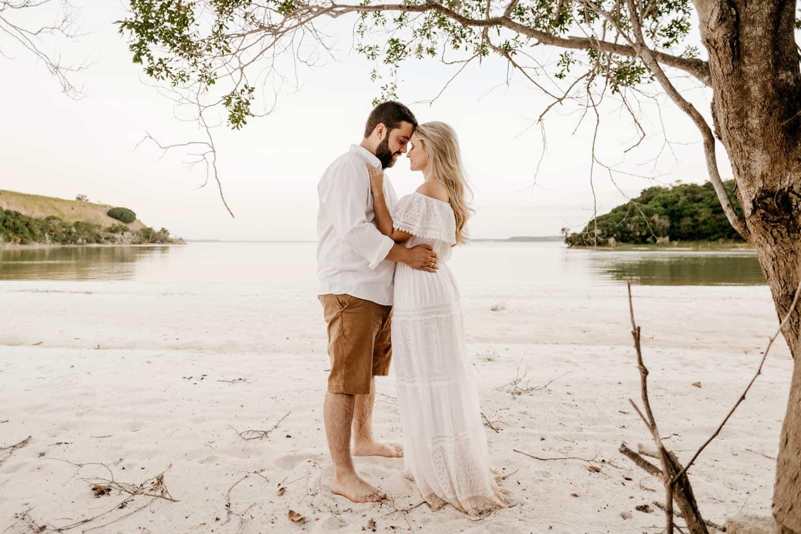 Ein Mann und eine Frau umarmen sich tagsüber am Strand