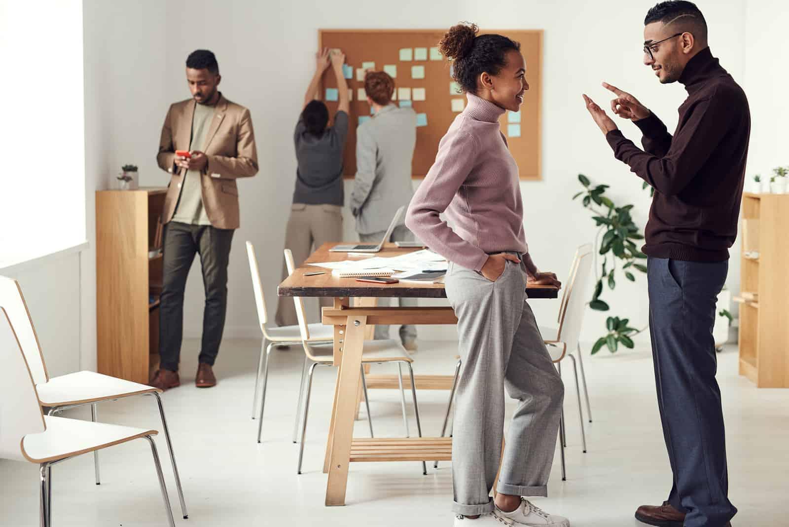 Ein Mann und eine Frau unterhalten sich bei der Arbeit im Besprechungsraum
