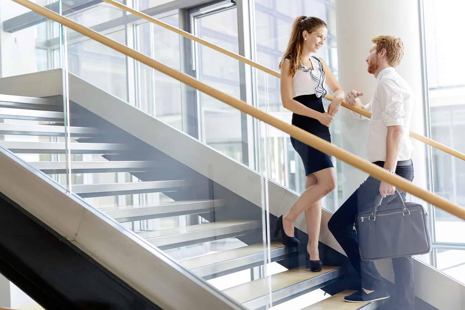 Ein Mann und eine Frau unterhalten sich auf Treppen und flirten