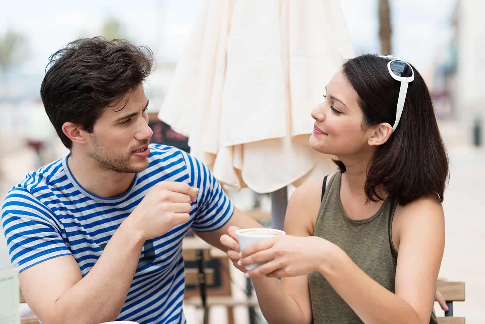 Ein Mann und eine Frau unterhalten sich in einem Café und trinken Kaffee