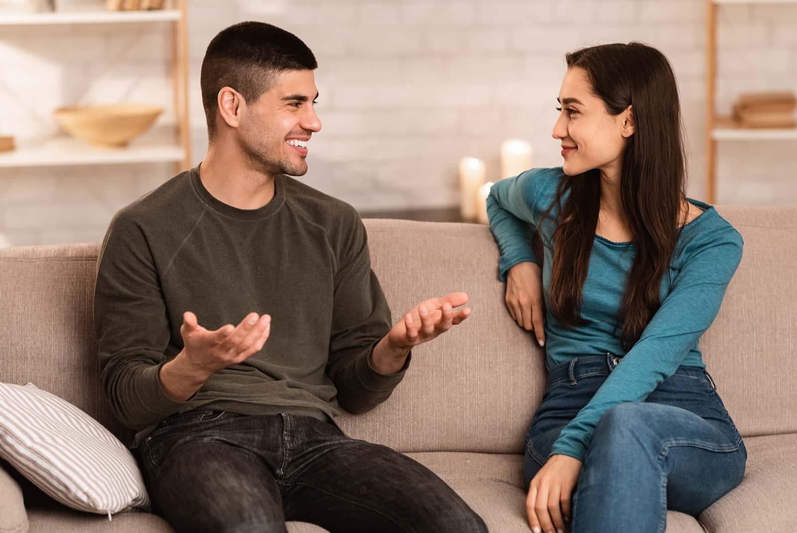 Ein Mann und eine Frau unterhalten sich nett auf der Couch in einer Wohnung sitzen