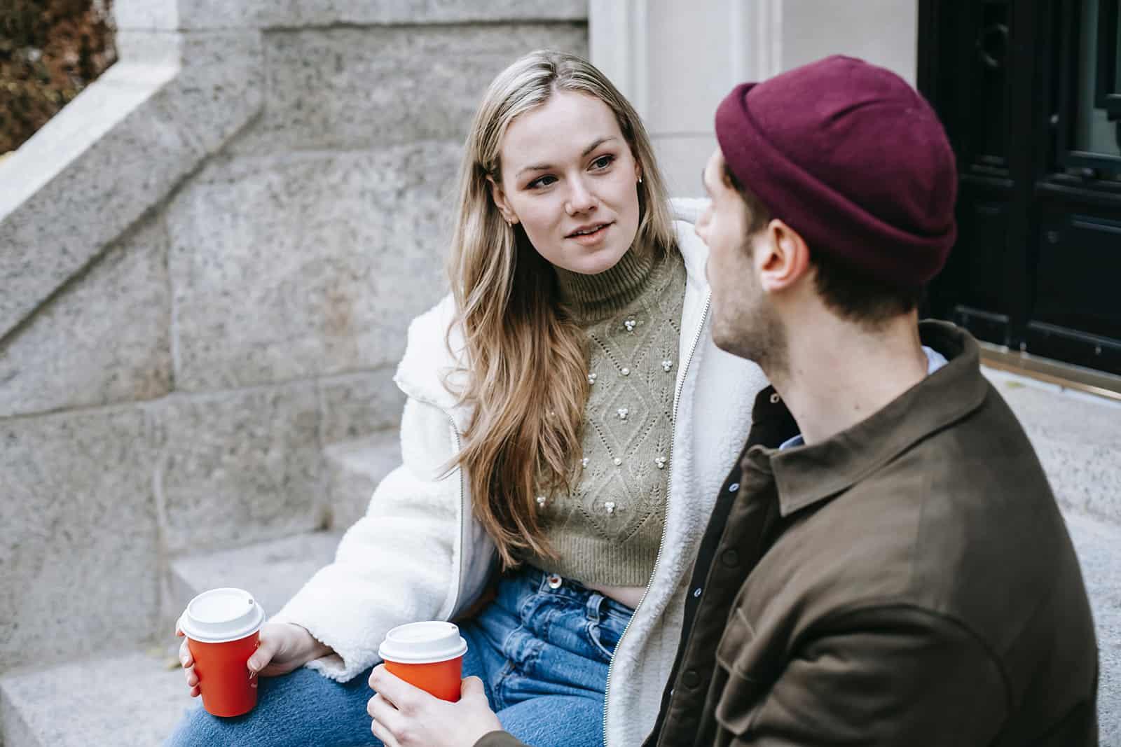 Ein Mann und eine Frau unterhalten sich über ein Date, während sie auf der Treppe sitzen