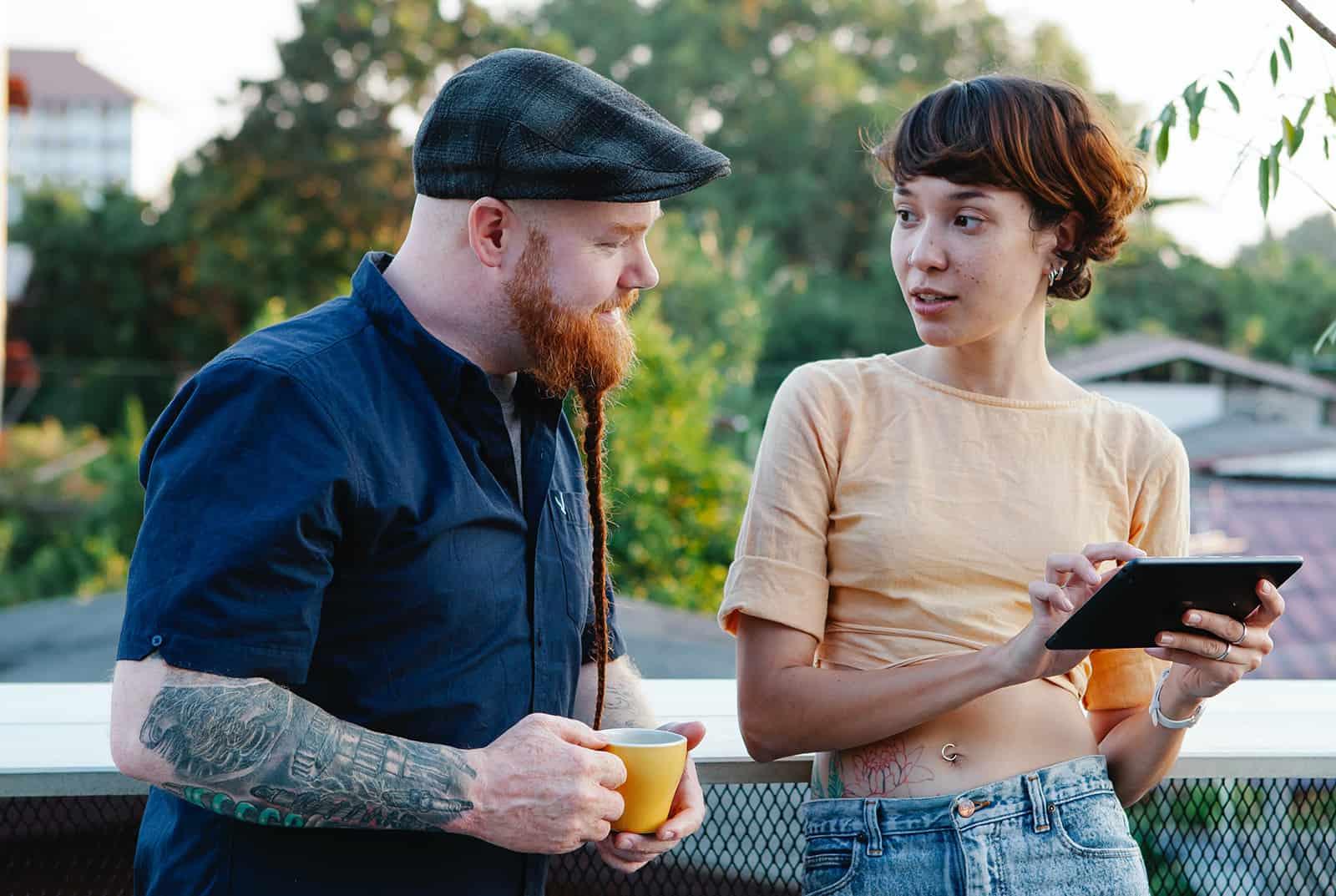 Ein Mann und eine Frau unterhalten sich und benutzen ein Tablet auf einer Terrasse