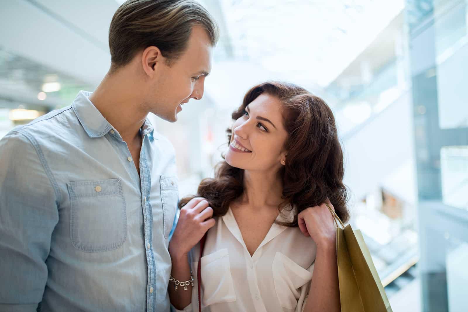 Ein Mann und eine lächelnde Frau sehen sich beim gemeinsamen Gehen an