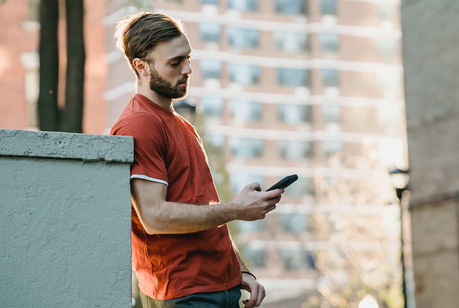 Ein bärtiger Mann, der ein Smartphone betrachtet, während er in der Stadt steht