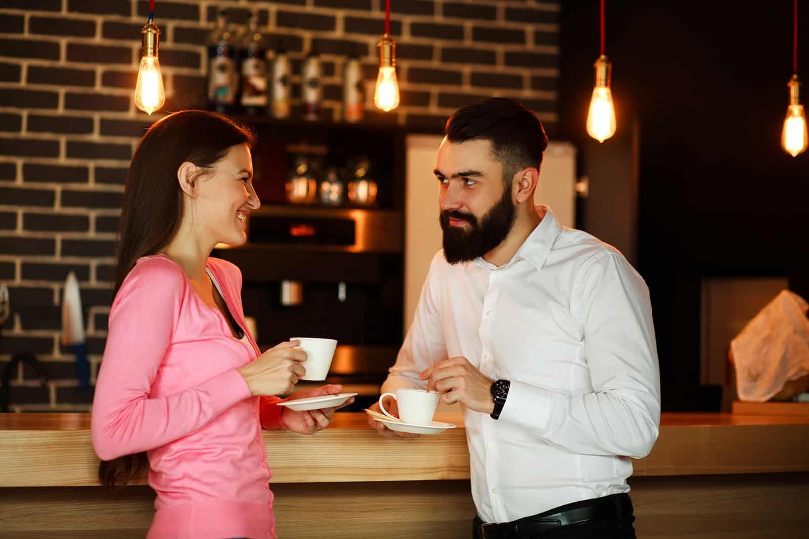 Ein lächelnder Mann und eine lächelnde Frau, die sich ansehen und im Café flirten