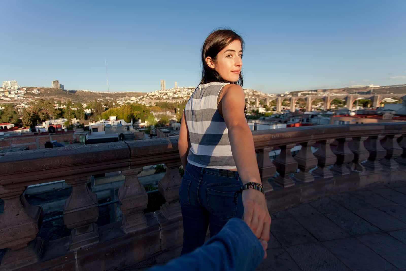 Eine Frau, die Hand mit einem Mann hält, während sie auf dem Balkon steht