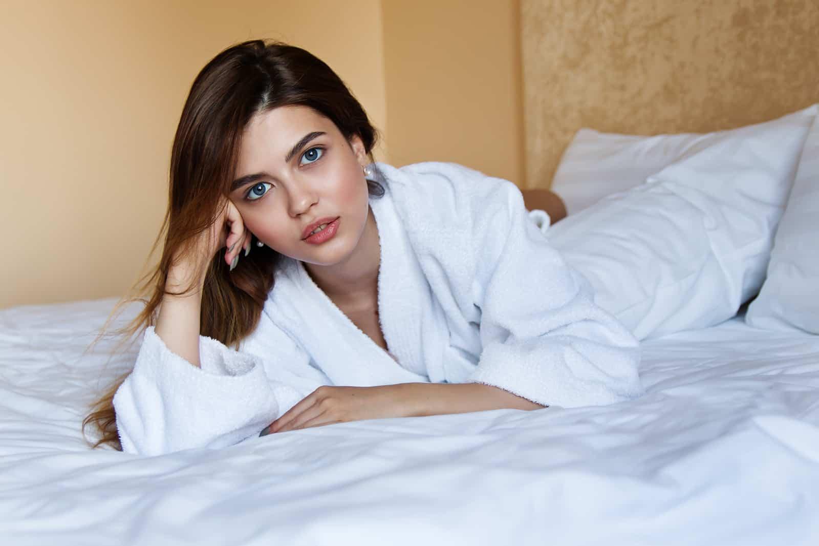 Eine Frau, die beim Nachdenken auf dem Bett liegt