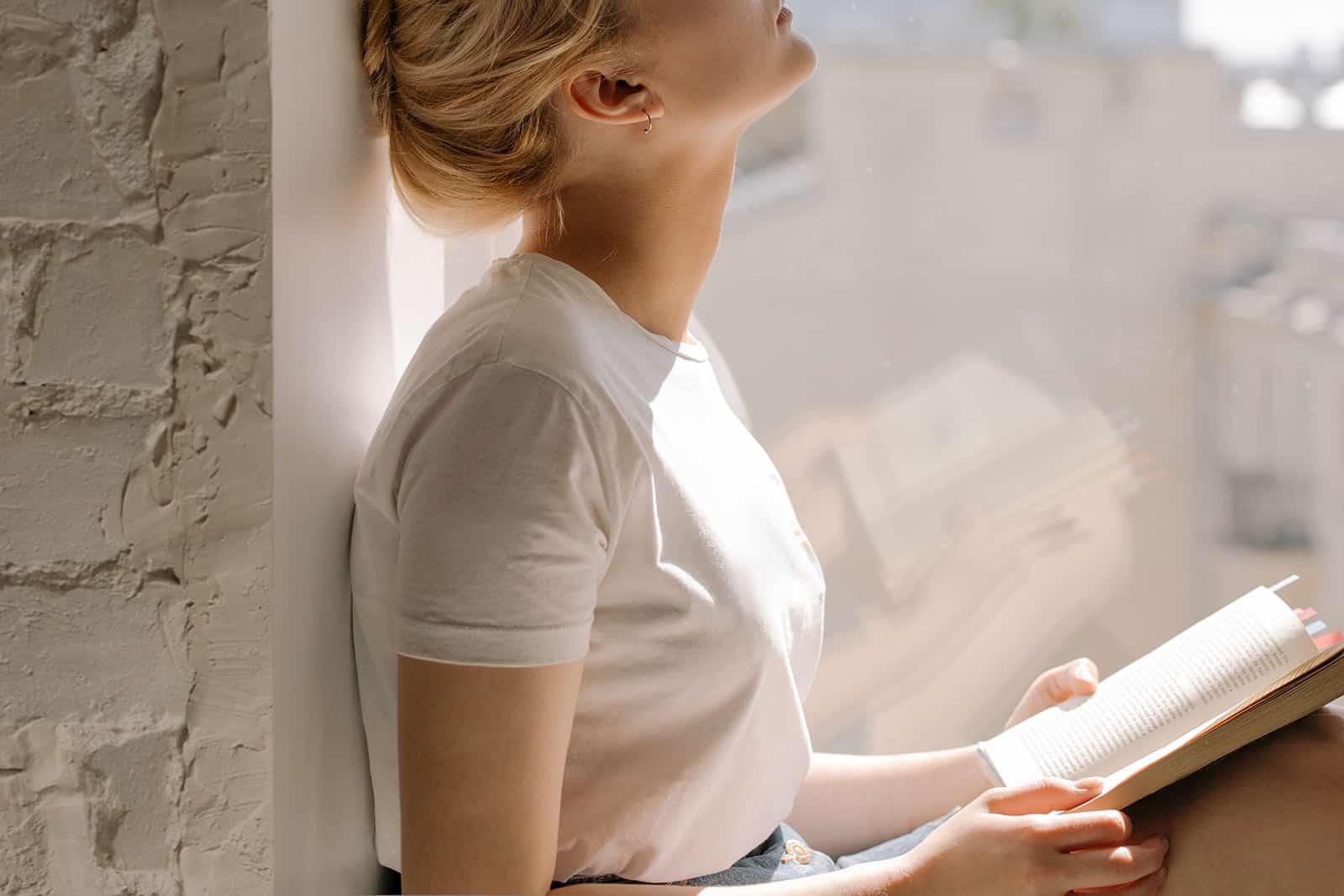 Eine Frau mit einem Buch auf dem Fensterbrett sitzen
