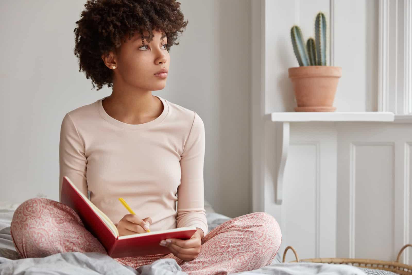 Eine schwarze Frau mit lockigem Haar sitzt auf dem Bett