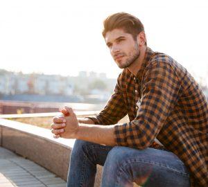hübscher junger Mann, der draußen sitzt