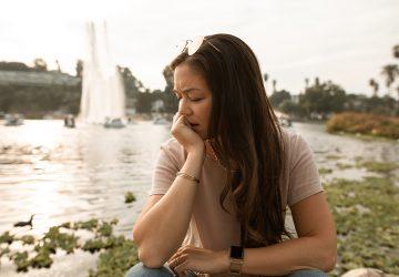 enttäuschte Frau sitzt in der Nähe des Sees
