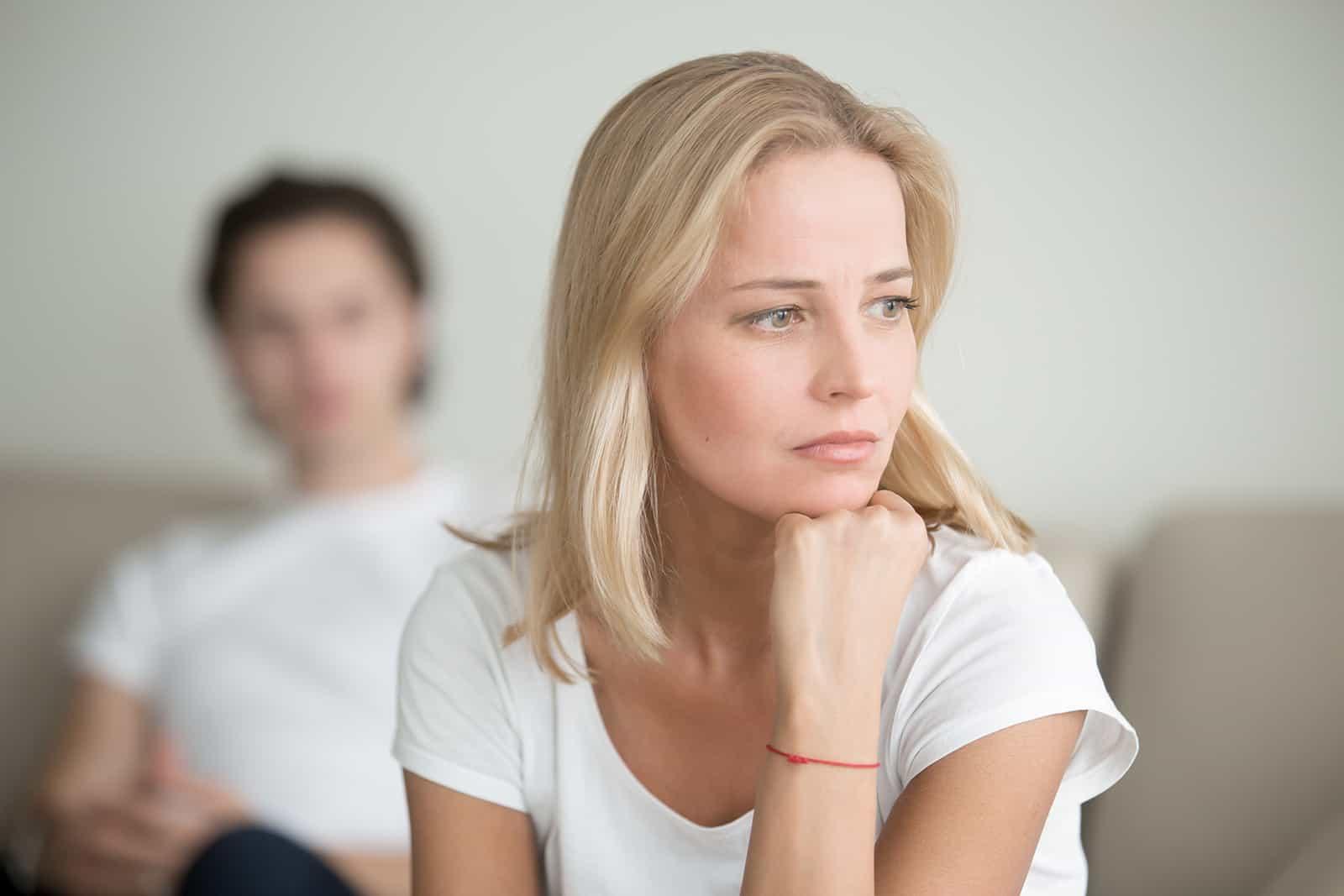 Ernsthafte traurige Frau, die über ein Problem nachdenkt, während ein Mann hinter ihr sitzt
