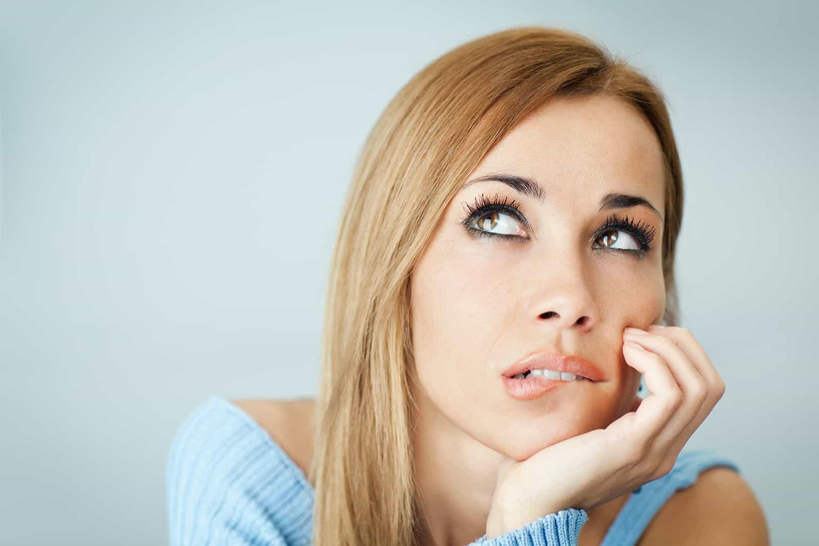 Frau denkt und beißt sich auf die Lippen und schaut mit einer Hand auf die Wange