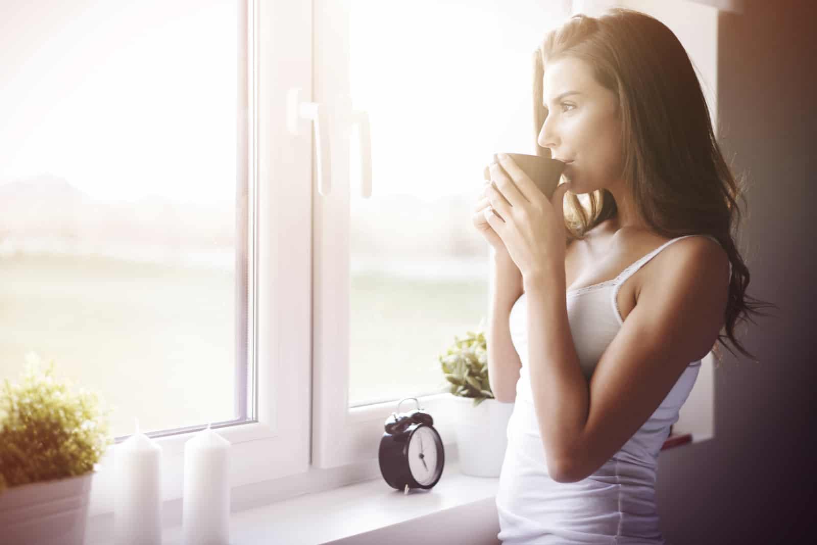 Frau, die Kaffee am Fenster trinkt