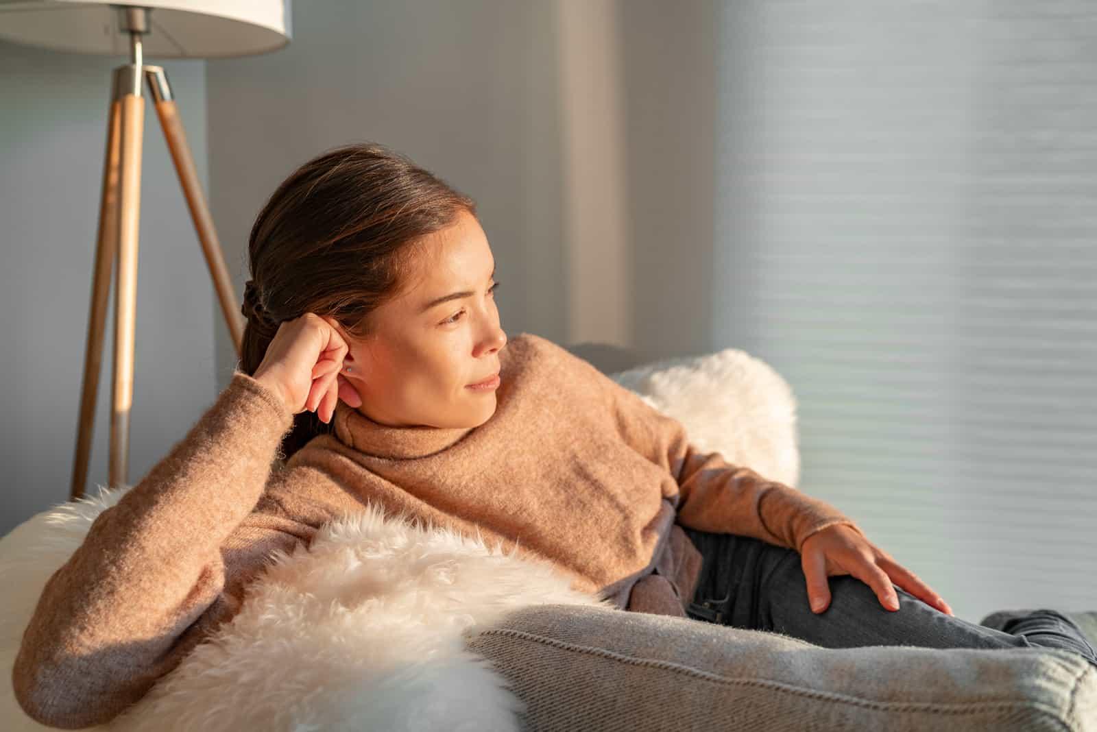 Frau entspannt nachdenklich aus dem Fenster schauen