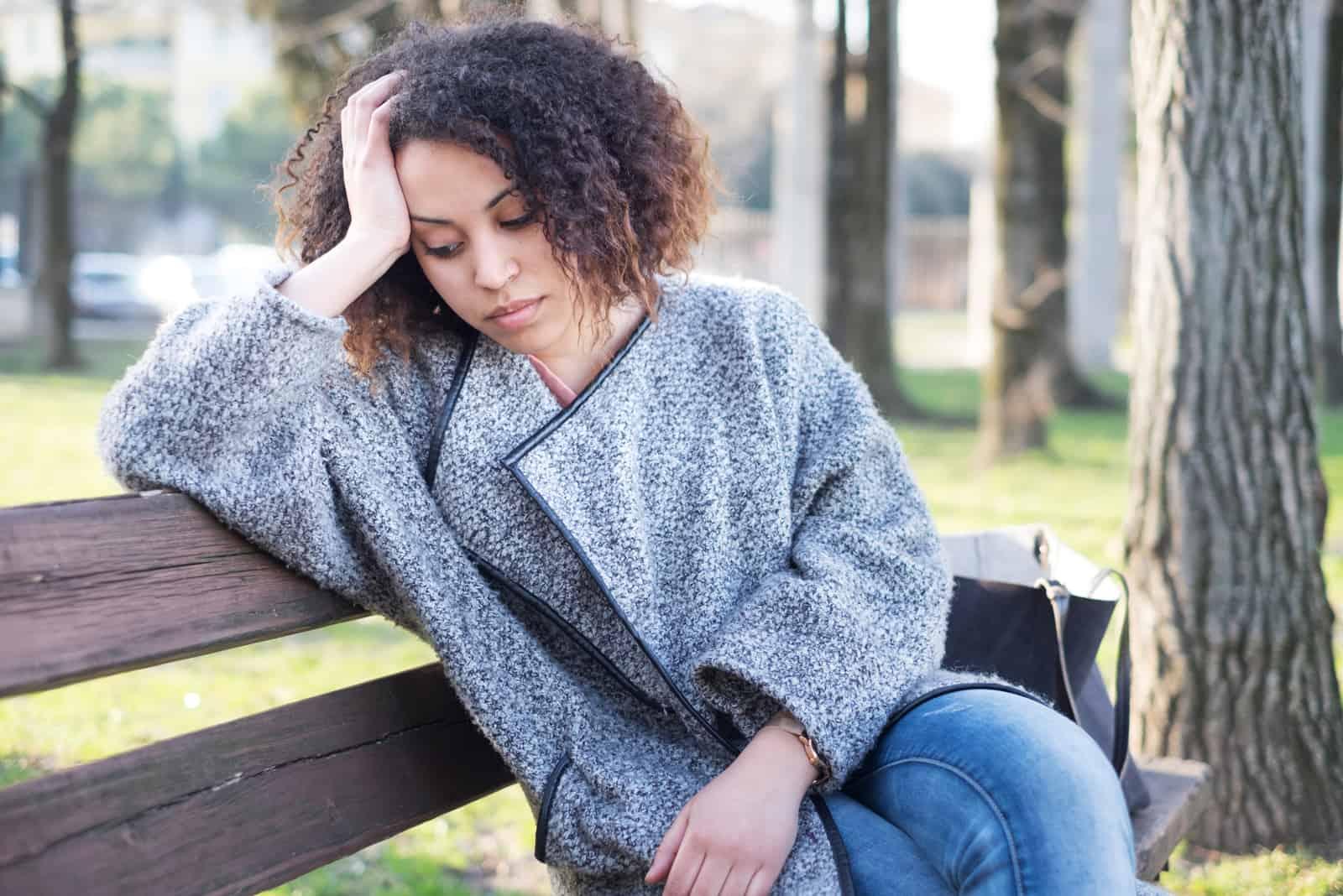 Frau sitzt alleine auf einer Bank im Park