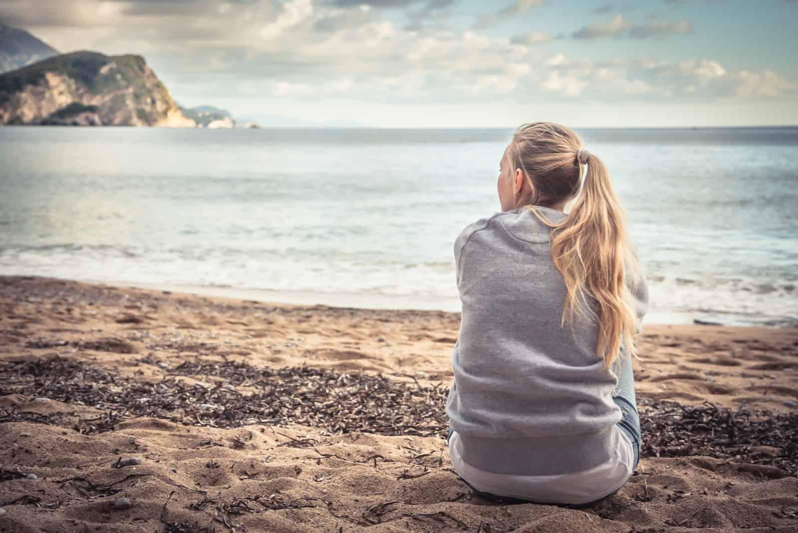 Frau sitzt am Strand und umarmt ihre Knie