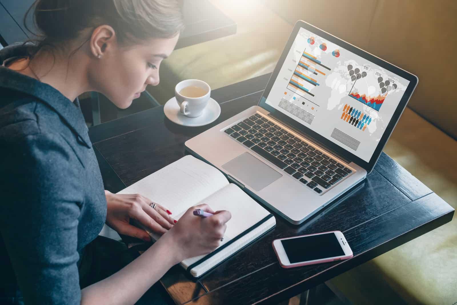 Geschäftsfrau, die am Tisch sitzt und Notizen im Notizbuch macht