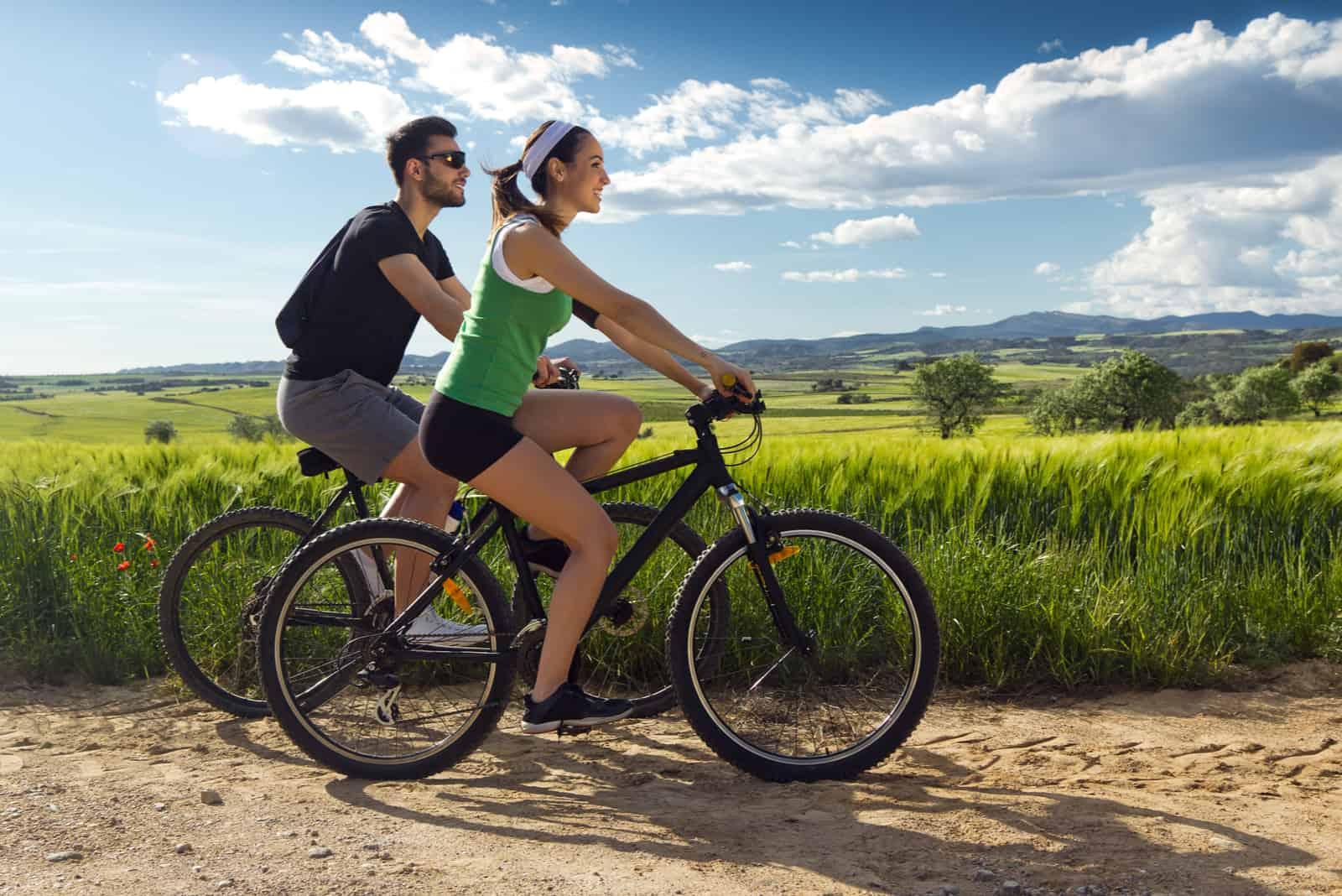 Glückliches junges Paar auf einer Radtour in der Landschaft