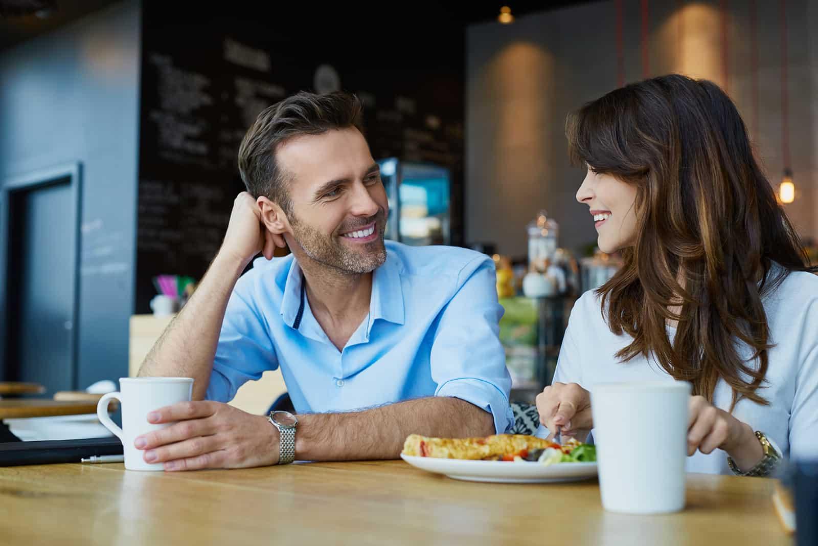 Glückliches Paar, das im Café spricht und zu Mittag isst