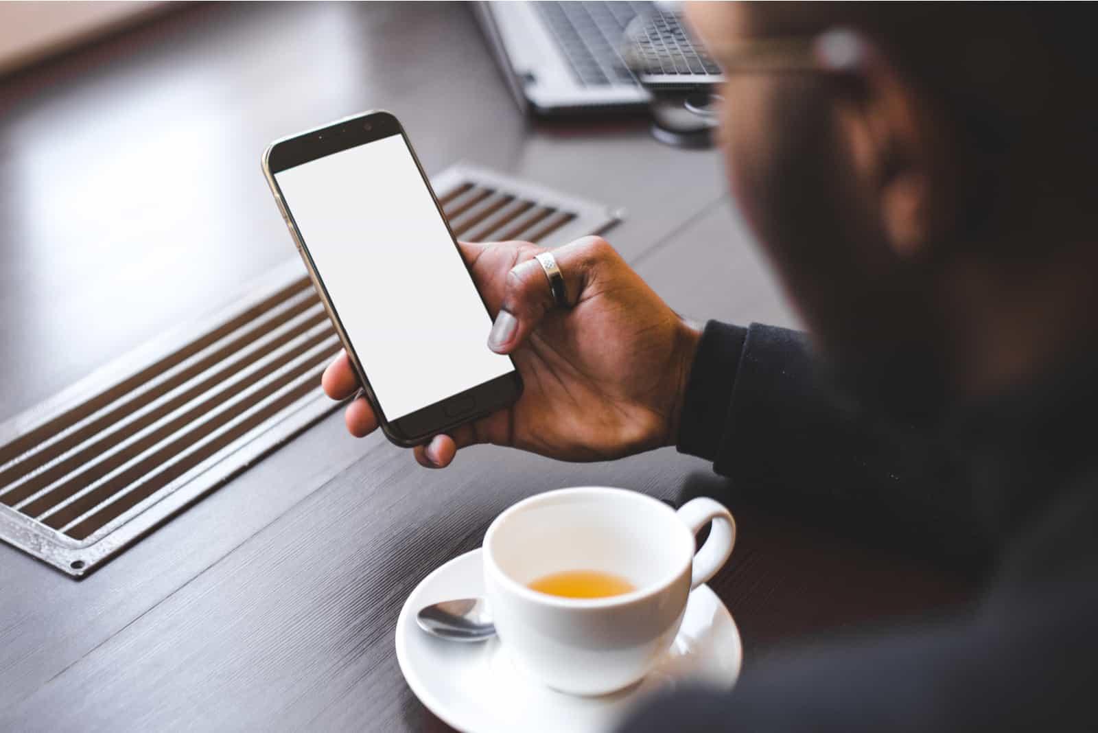 Mann, der Kaffee hält Telefon hält