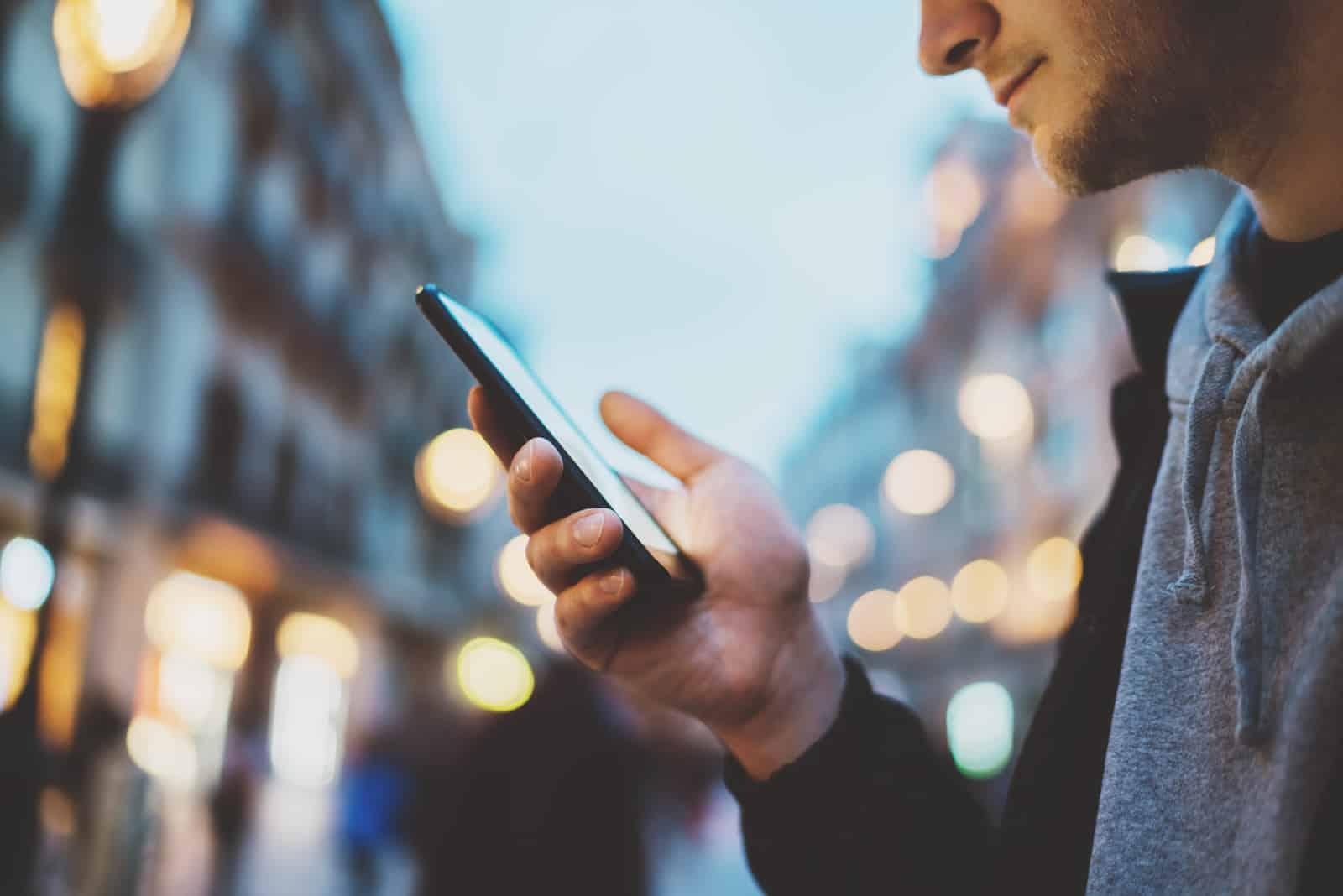 Mann mit Smartphone in der Nacht Stadtstraße