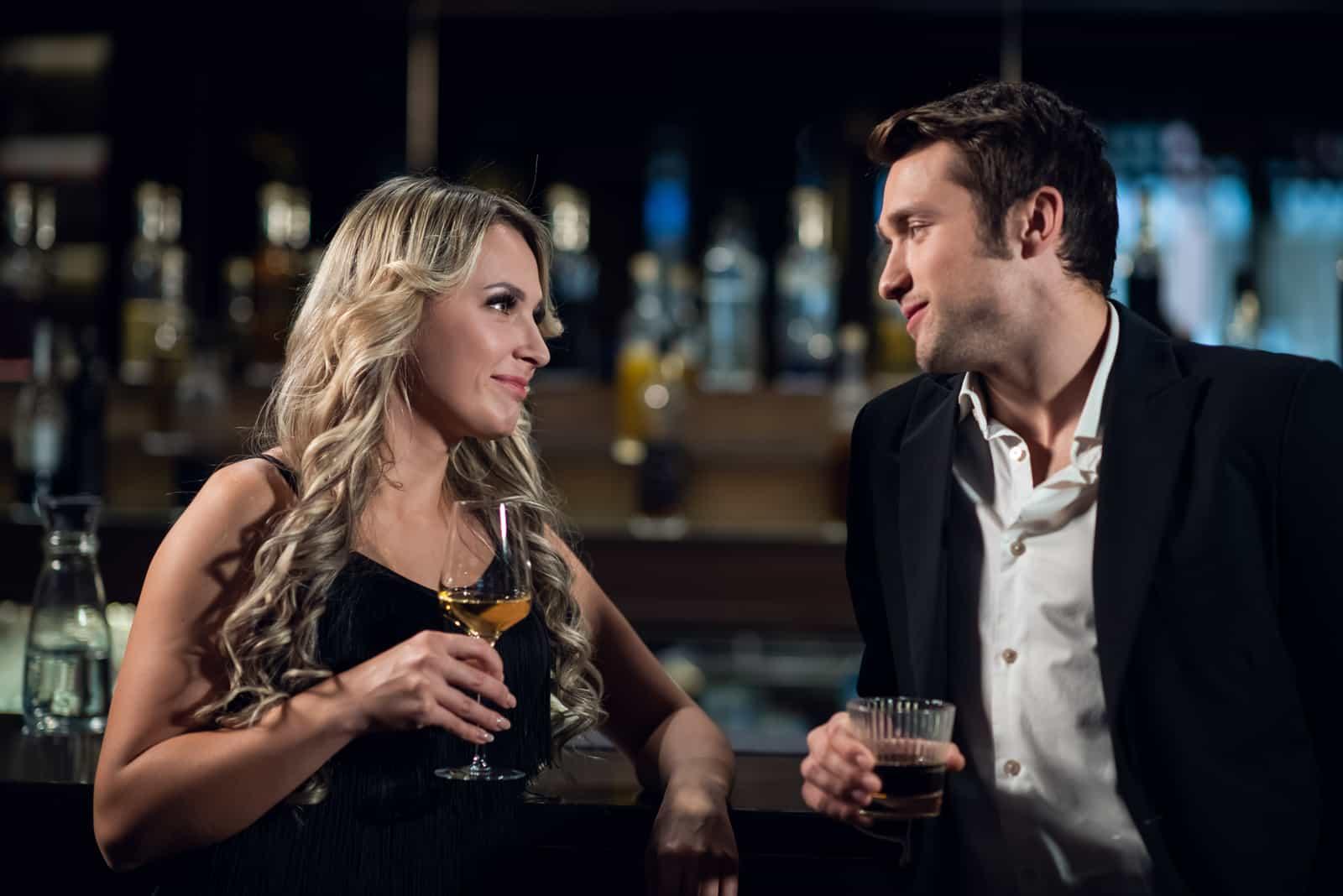 Mann und Frau an der Bar trinken Cocktails