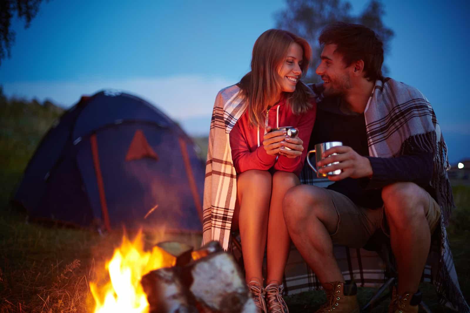 Paar Camping, am Feuer sitzen