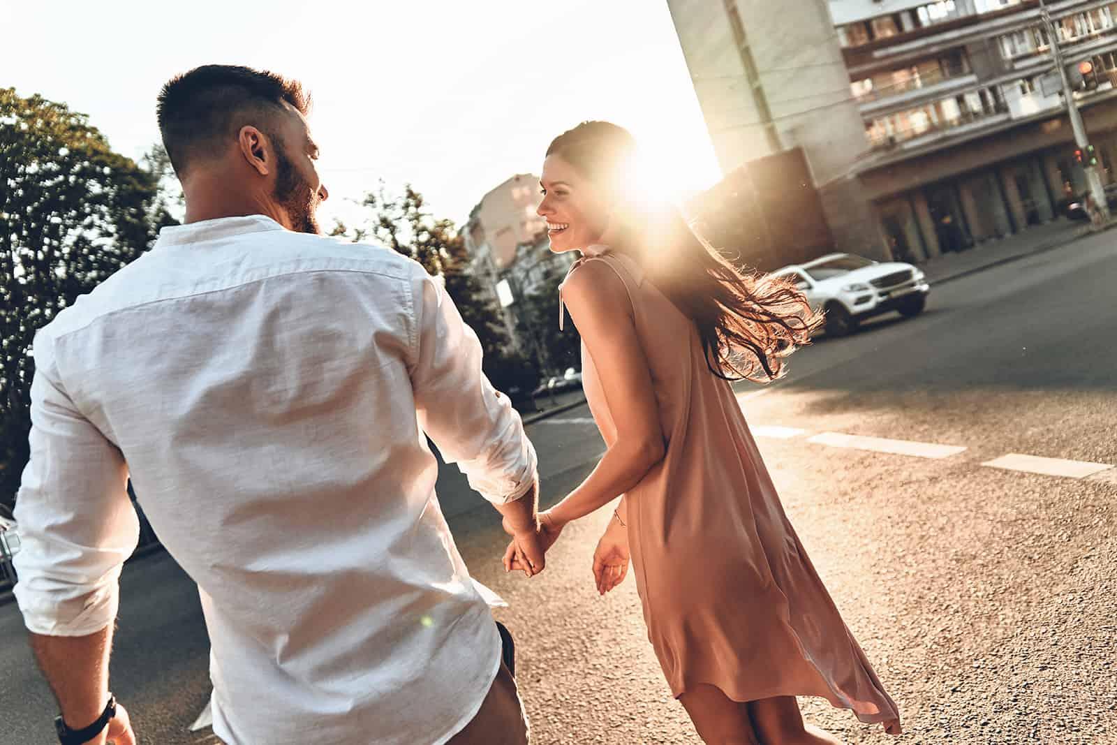 Paar Händchen haltend und einander ansehend beim gemeinsamen Gehen