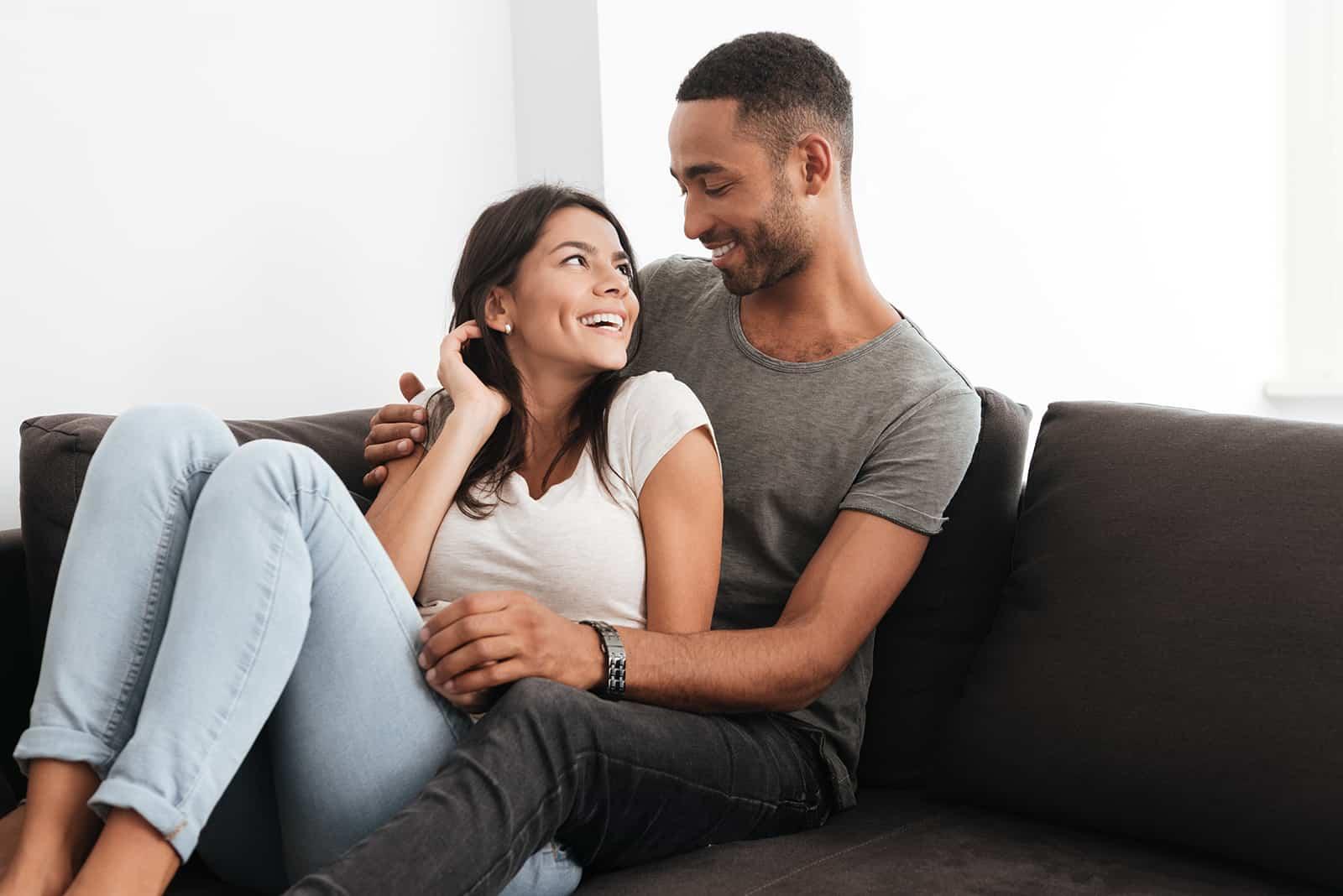 Paar lacht zu Hause auf einem Sofa und schaut sich an