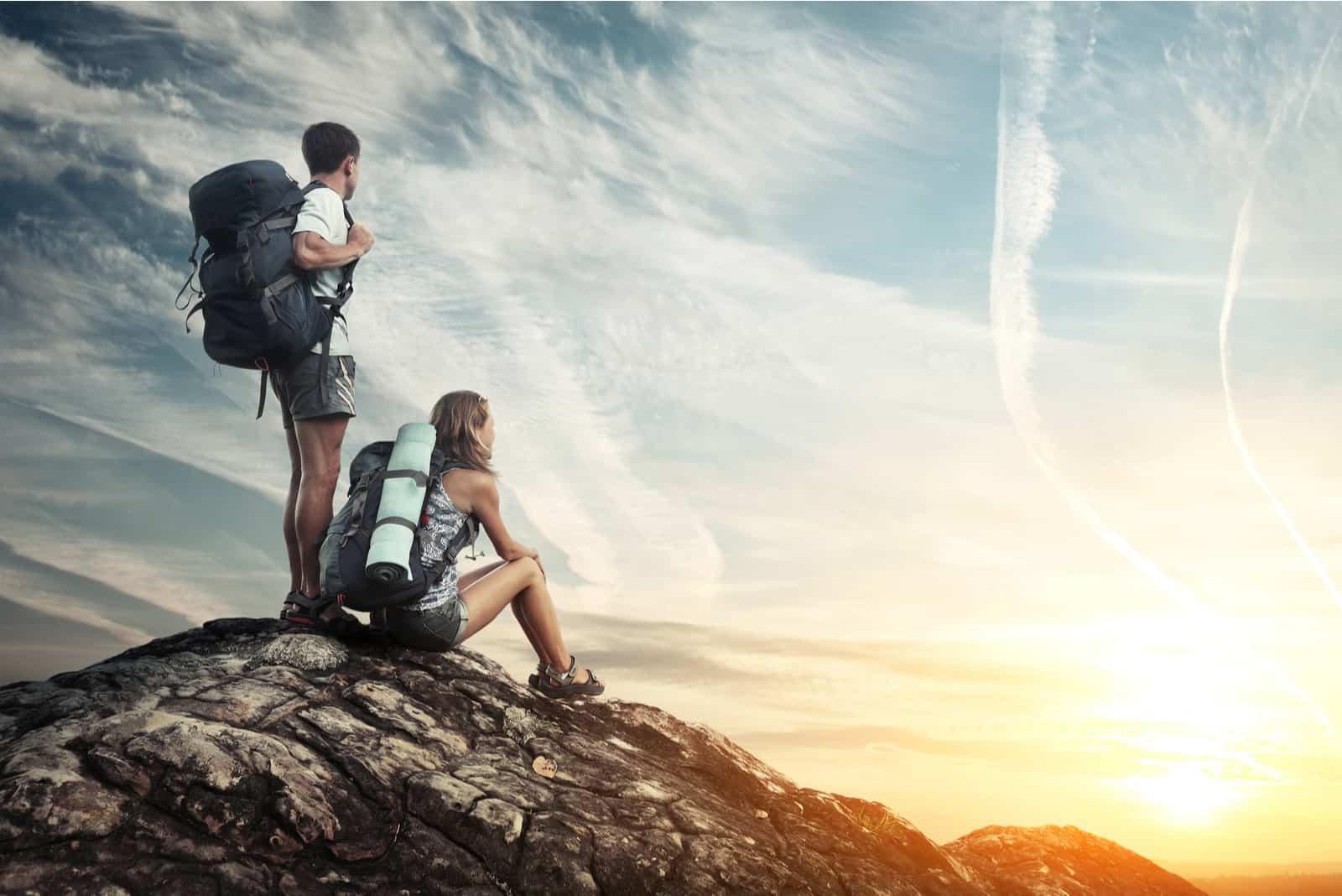 Paar mit Rucksäcken genießen Sonnenuntergang auf einem Berg