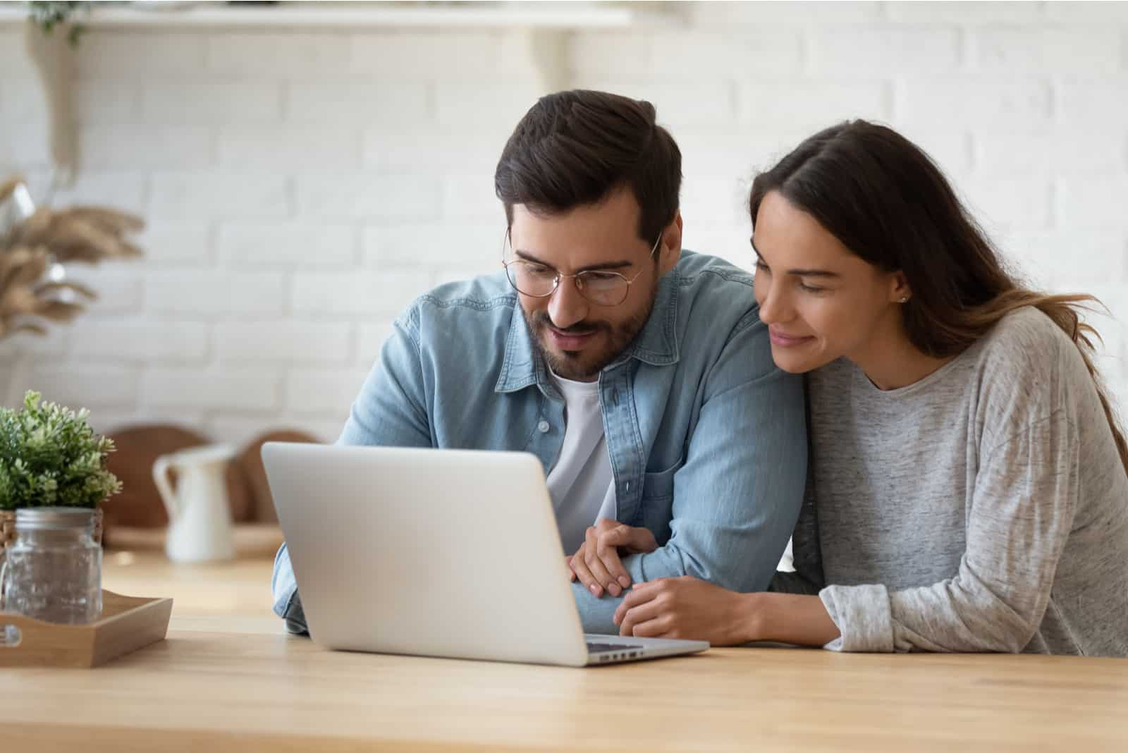 Paar sitzt und schaut auf Laptop-Bildschirm