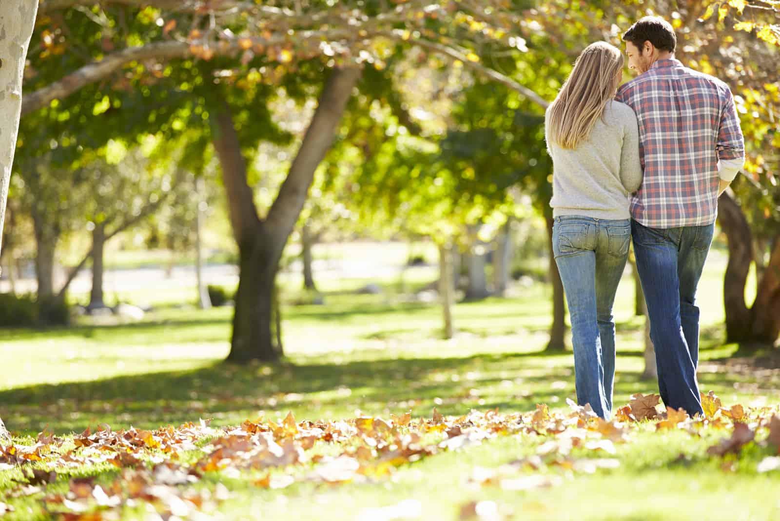 Romantisches Paar, das durch Herbst-Wald geht