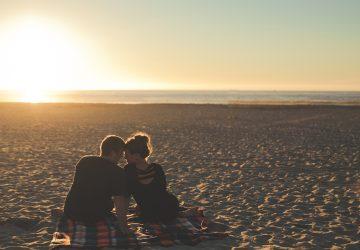 ein Mann und eine Frau sitzen am Strand während des Sonnenuntergangs