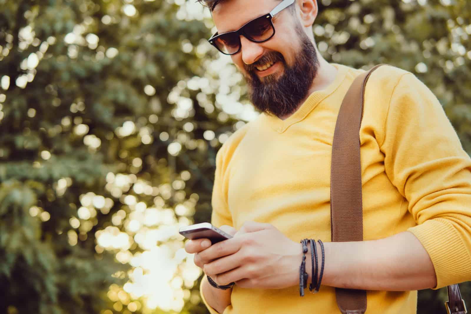 Schöner Mann Bart mit Smartphone in der Hand