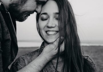 Ein lächelndes Mädchen schloss die Augen und ein Mann berührte ihr Gesicht