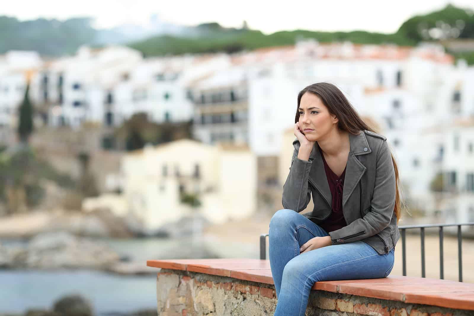 Traurige nachdenkliche Frau, die weg schaut, die auf einem Sims in einer Küstenstadt sitzt