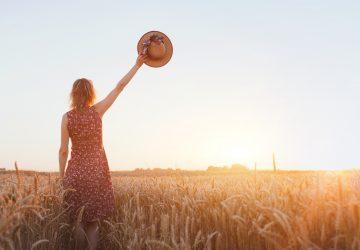 Frau winkt Hand auf dem Feld